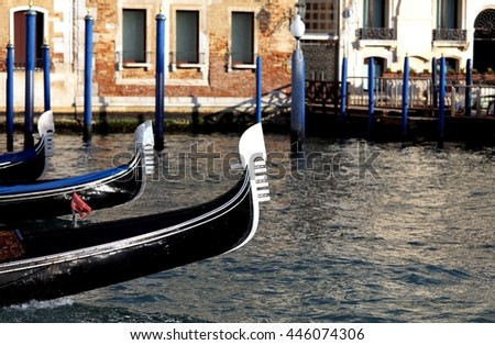 three Venetian gondolas sailing the waters of the Grand Canal in Venice
