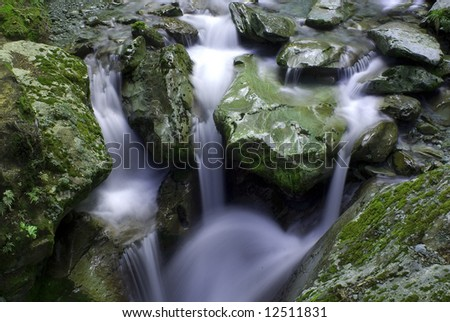 Three waterfalls flowing into one river in Mount Aspiring National Park - stock photo