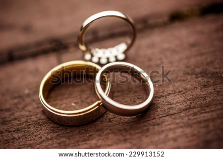 Three wedding rings on a wooden floor - stock photo