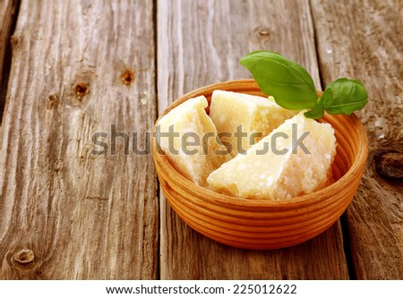 Three wedges of gourmet parmesan cheese or parmigiano reggiano, a regional speciaility from Italy, in a pottery bowl on a wooden table with copyspace - stock photo