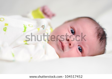 Three Week Old Baby Boy. Infant laying on white blanket looking at viewer. Shallow DOF. - stock photo