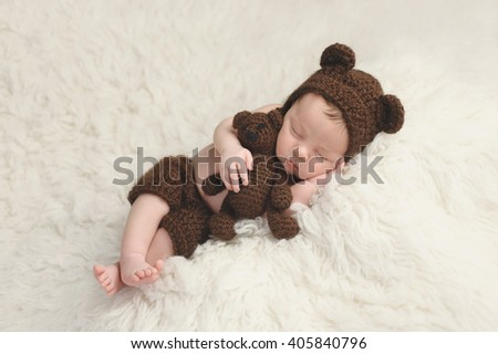 Three week old newborn baby boy wearing a brown, crocheted bear hat and shorts. He is sleeping on a white flokati rug and holding a matching stuffed bear toy.