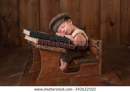 Three week old newborn baby boy wearing crocheted cap, shorts and suspenders. He is sitting at a tiny school desk and sleeping on a stack of vintage books. - stock photo