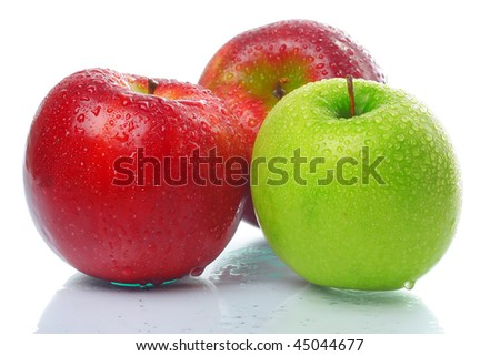 Three wet apples on glass surface over white - stock photo