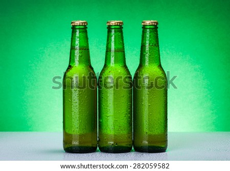 Three wet blank beer bootles on backlit green background - stock photo