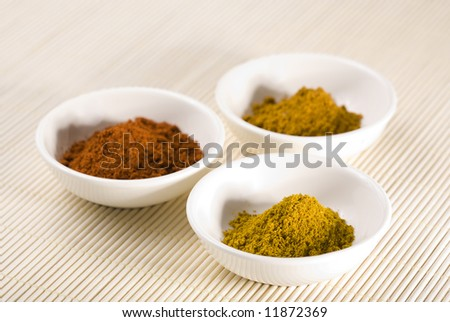 three white bowls filled with curry, turmeric and cayenne pepper