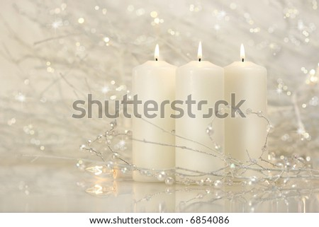 Three white candles with shimmering background for the holidays - stock photo
