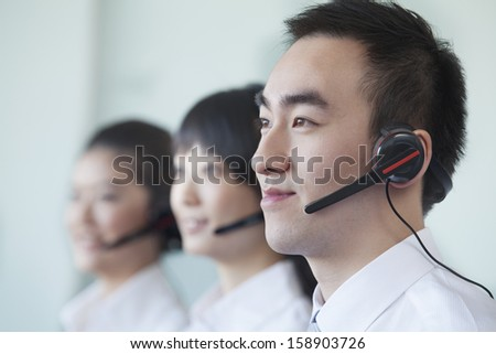 Three white collar workers in row with headsets