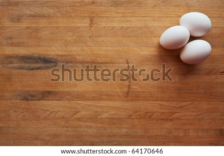 Three white eggs sit on a butcher block counter with area suitable for text - stock photo