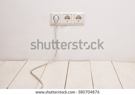 Three white electrical outlets with white power cord and plug on white wall. - stock photo