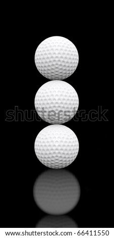 Three white golf balls stacked on top of each other sitting on a glossy black floor.