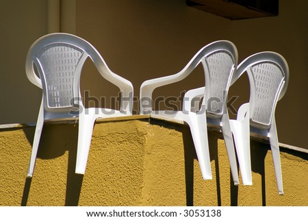 Three white plastic chairs drying on balcony
