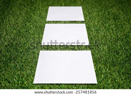Three white sheets of paper on the grass - stock photo
