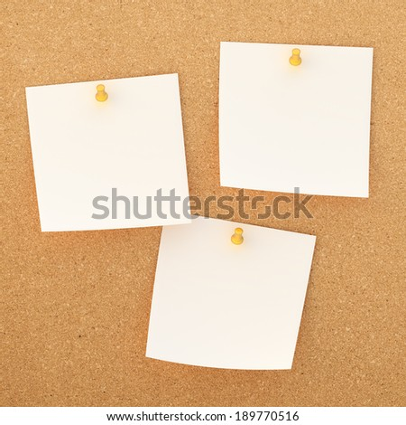 Three white square paper notes sticked with the orange office pins to the cork board background - stock photo