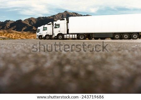 Three white trucks on a parking lot of a transportation company waiting for the next order. Low angle shot, copy space on the bottom of the image - stock photo