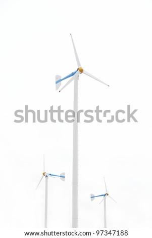Three white wind turbine generating electricity on isolated background. - stock photo