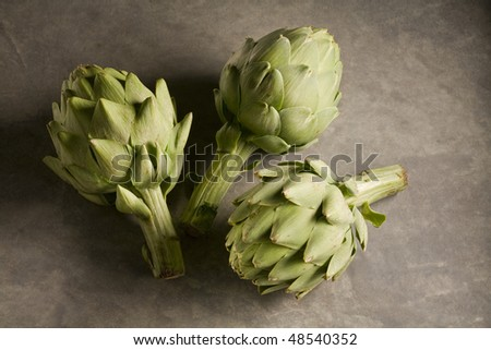 Three whole artichokes on marble surface - stock photo