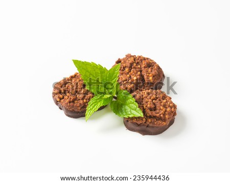 three whole grain cookies dipped in dark chocolate and decorated with piece of mint - stock photo