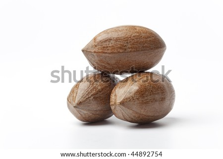 Three whole pecan nuts on white background