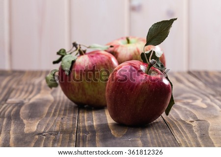 Three whole vivid red yellow ripe apples with smooth peel and green leaves on stalks on wooden table on white wall background, horizontal photo - stock photo