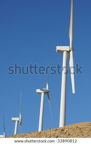 three wind turbines at top of hill against blue sky - stock photo