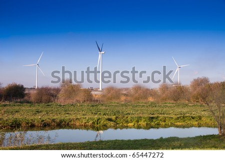 Three Wind turbines in English countryside  on  blue sky autumn day with canal in foreground - stock photo