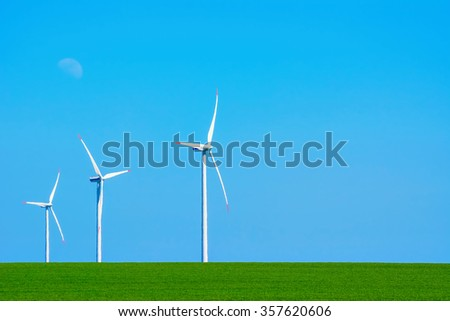 Three Wind Turbines in heat haze against of Blue Sky - stock photo