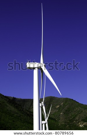 Three wind turbines or windmills against a blue sky