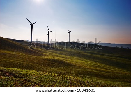 Three wind turbines silhouettes on top of hill