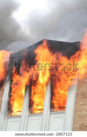 Three windows filled with flames in a Detroit apartment - stock photo