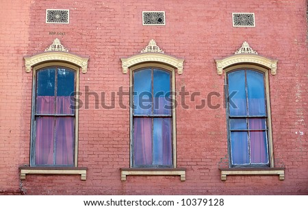 Three windows in brick wall of antique building - stock photo
