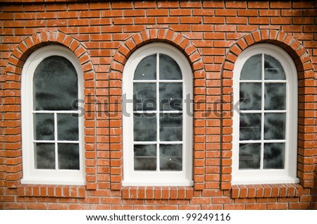 three windows on the red brick wall - stock photo