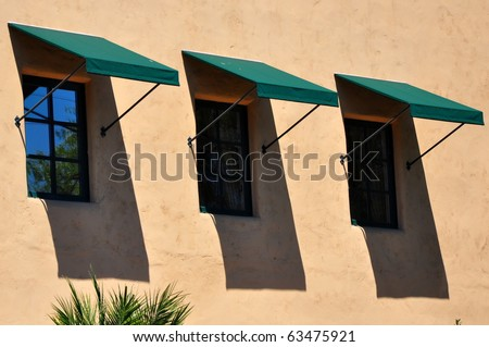 Three windows with awnings against terra cotta colored wall - stock photo