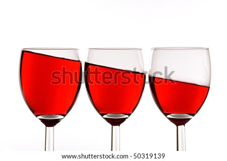 Three wineglasses filled with red wine, surface of liquid is slanted