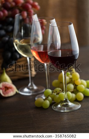 Three wineglasses of red, rose and white wine , grapes in wicker basket and figs on brown wood textured table covered with canvas towel - stock photo
