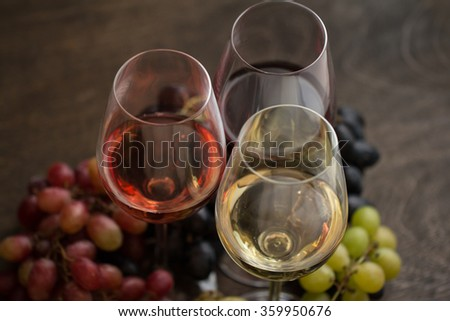 Three wineglasses of red, rose and white wine with three kinds of grapes on brown wood textured table - stock photo