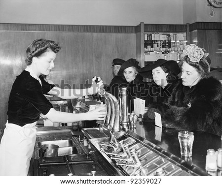 Three woman and a man sitting in a soda fountain - stock photo