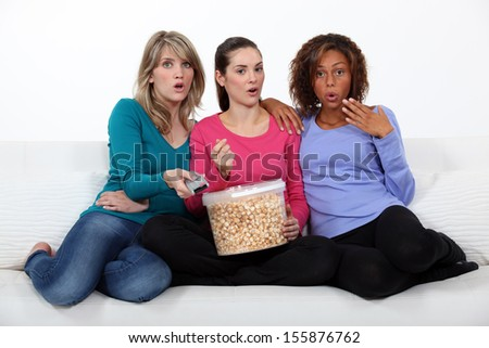 Three woman eating popcorn whilst watching film - stock photo