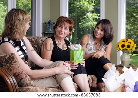 Three Woman Giving A Surprise Gift To Their Friend - stock photo