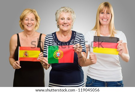 Three Woman Holding Different Flag On Gray Background - stock photo