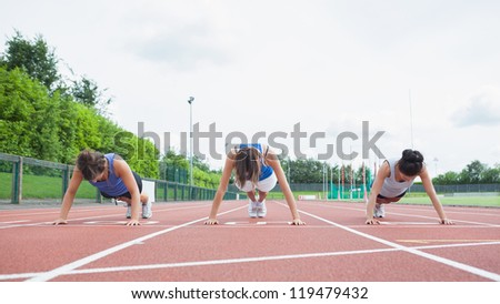 Three woman stretching on running track in stadium