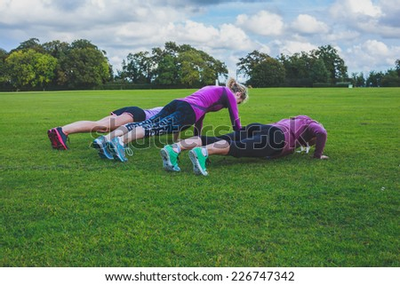 Three women are doing push ups on the grass in the park - stock photo