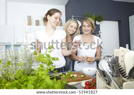 three women cook in kitchen