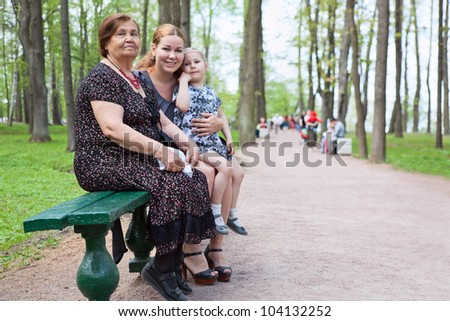 Three women different ages are sitting on bench in park. Grandmother, mother and small daughter - stock photo
