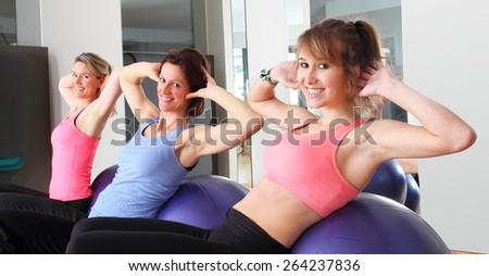 Three women doing exercise on balls in fitness center - stock photo