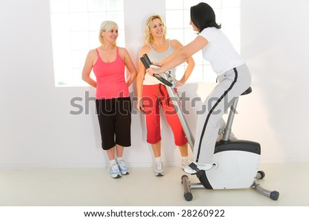 Three women dressed sportswear. One of them exercising on bike.