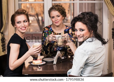 Three women friends in cafe make dialogue and smile over joke