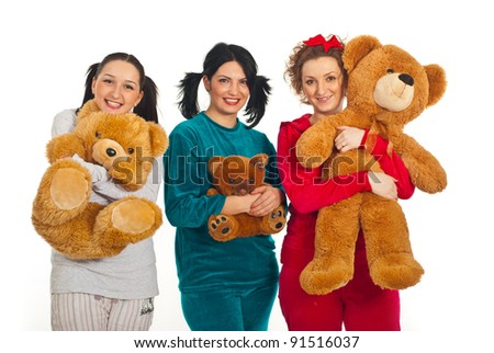 Three women in pyjamas holding teddy bears and smiling isolated on white background - stock photo