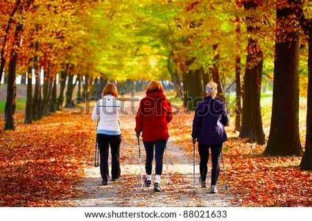 Three women in the park - Nordic walking - stock photo