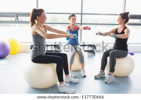 Three women lifting weights together on exercise balls in gym - stock photo